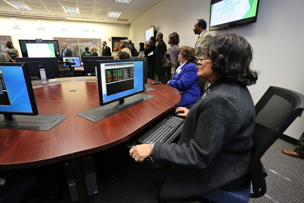 Jackson State University President Dr. Carolyn W. Meyers tries her hand at a state-of-the-art trading floor terminal in the College of Business at its grand opening Nov. 14, 2014. (Photos by Charles A. Smith)
