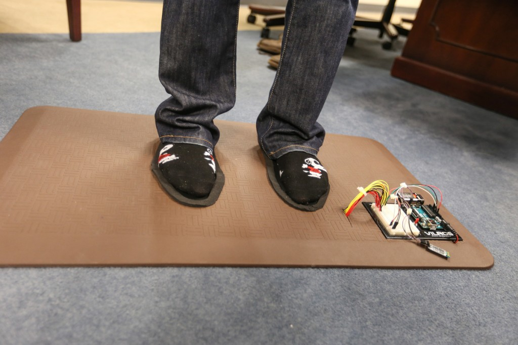 Smart Mat2: Standing on the prototype, Baker shows how the feet are positioned for reading by an Android app. (Photo by Charles A. Smith/JSU)