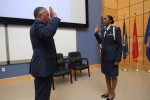 Col. Dewey Holmes (Ret.) of Arizona administers the oath elevating Air Force ROTC cadet Brittany Lynn to second lieutenant during her commissioning and pinning ceremony. Lynn will now train to become a combat systems officer. (Photo by Charles A. Smith/JSU)