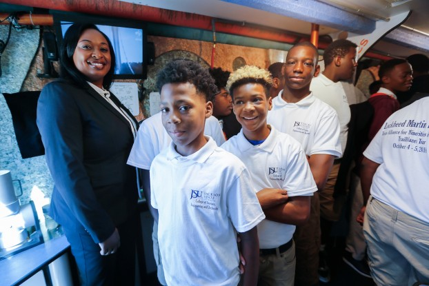JPS students join Lockheed executive and JSU alum Karmyn Norwood inside a science museum on wheels called Trailblazers, parked on the main campus outside. The trailer provides information on energy, space, weather, biotechnology and aerodynamics. (Photo by Charles A. Smith/JSU)