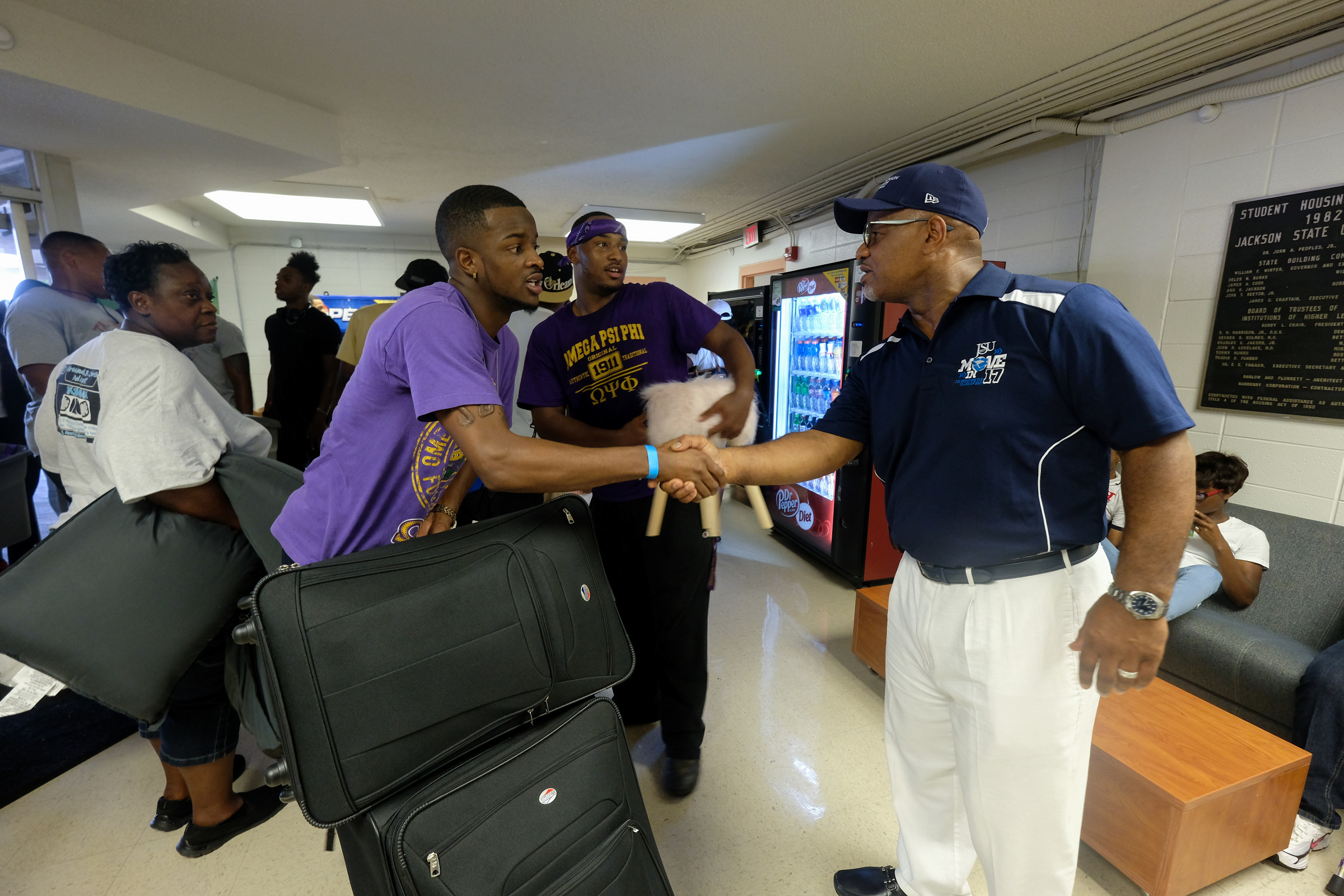 JSU President William B. Bynum, Jr., greets student-volunteer DaQuan Powell in the lobby of McAlister-Whiteside. Bynum  believes that in order to lead, students must also know how to serve. (Photo by Charles A. Smith/JSU)