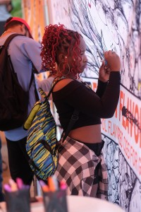 A student signs her name on the Truth mural making a pledge to abstain from smoking. (Photo by Charles A. Smith/JSU)