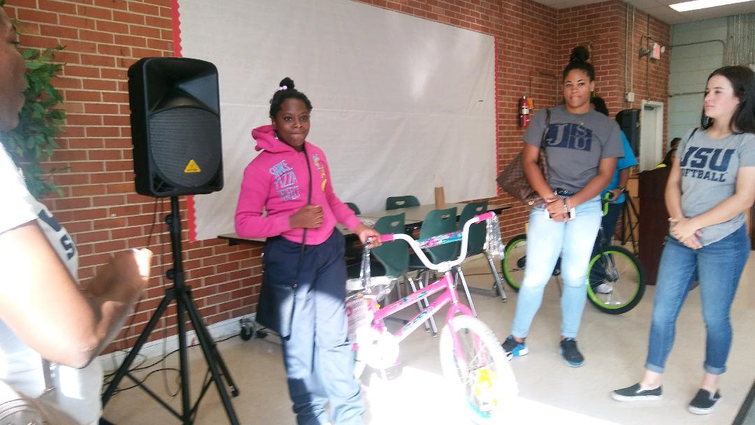 A student is honored for not missing a day of school. Each month, two students will be awarded a bicycle.