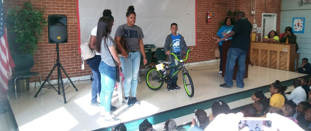 Another honored student proudly shows off his new bicycle.