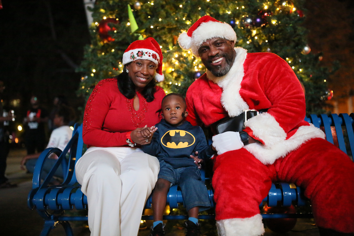 """Santa (Coach Derek Scott, associate athletic director for Internal Operations) and Mrs. Claus (Dr. Debra Mays-Jackson, vice president and chief of staff) bring excitement to a little boy with a big wish during JSU's annual """"Holidays Under the Stars."""" (Photo by Aron Smith/JSU)"""