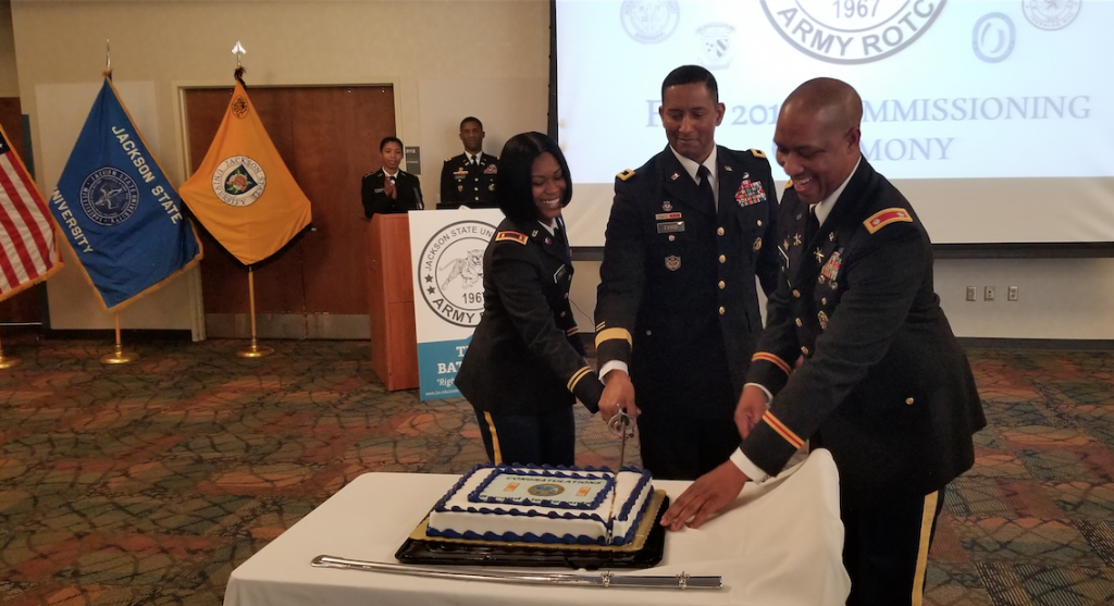 Lt. Col. Dexter M. Brookins, chair and professor of JSU's Military Science, assists with one of the sweetest parts of the ceremony. He's joined by Tashe'Wa N. Hill and Evans.