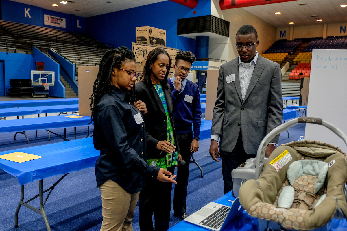 Dr. Jacqueline Stevens, a JSU biology professor in the College of Science, Engineering and Technology, discusses a project with students from Jim Hill High School. During the 45th Region II Science Fair, the students presented the Baby Beeper. One of its main features is to help ensure that a child is securely buckled in a car seat. (Photo by Charles A. Smith/JSU)