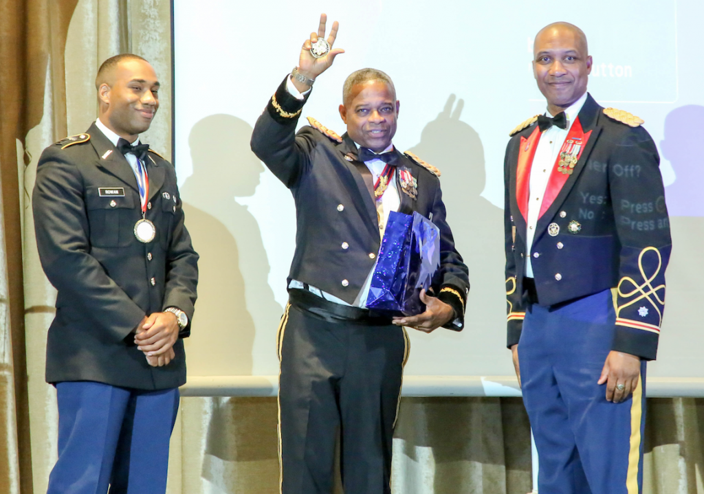 Cadet Keith Rowan, left, extends honors to Jones. They're joined by Lt. Col. Dexter Brookins, right, commander of the JSU Tiger Battalion.