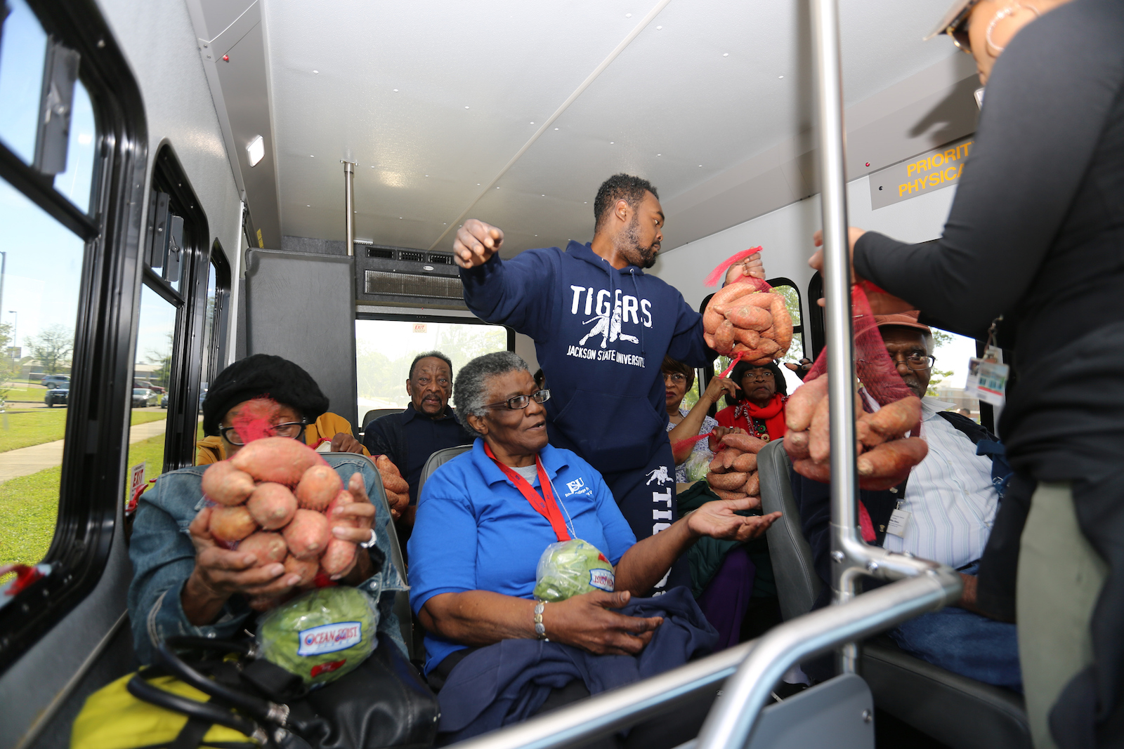 JSU distributes sweet potatoes and lettuce to senior citizens in a public transit vehicle. (Photo by Charles A. Smith/JSU)