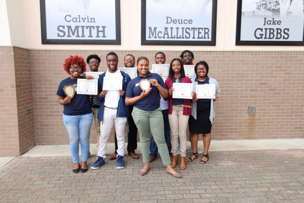 Staff members of JSU's student-led newspaper The Blue & White Flash show off the many awards they received from the Mississippi Press Association. (Photo special to JSU)