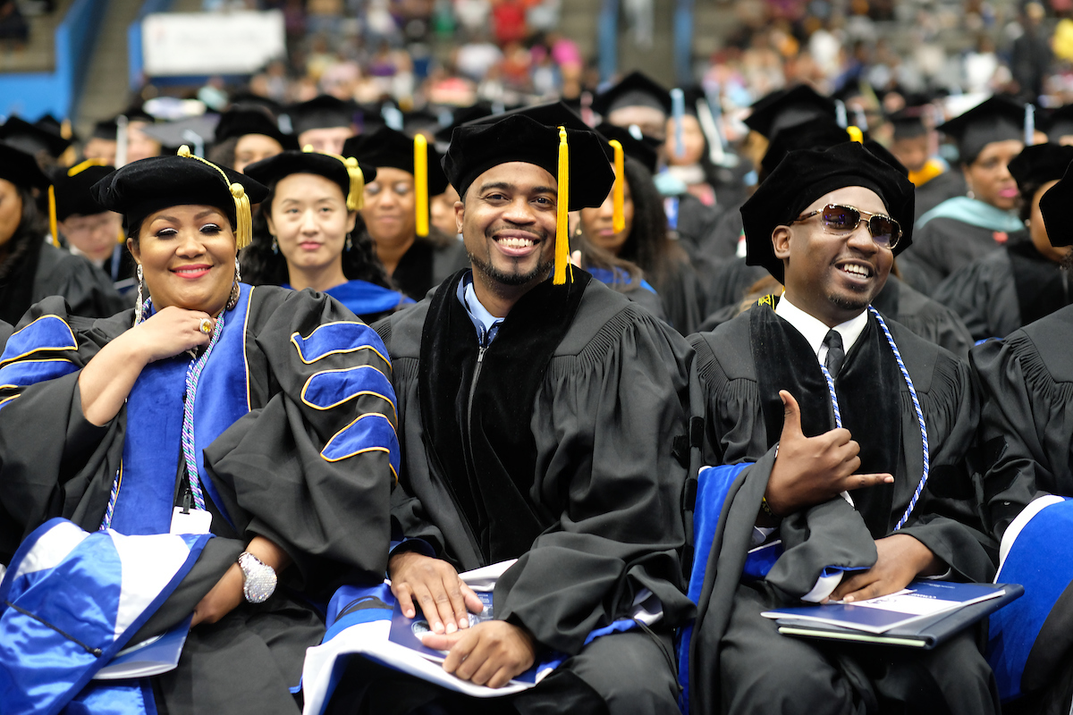 Verjaun P. Gordon, middle, celebrates with his peers as he prepares to receive his doctorate in education administration. (Photo by Charles A. Smith)