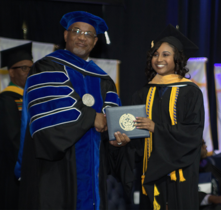 Tershuna Bass accepts her  Master's degree from JSU President Dr. William B. Bynum, Jr. just one year after receiving her Bachelor's degree. (Photo by Charles Smith)