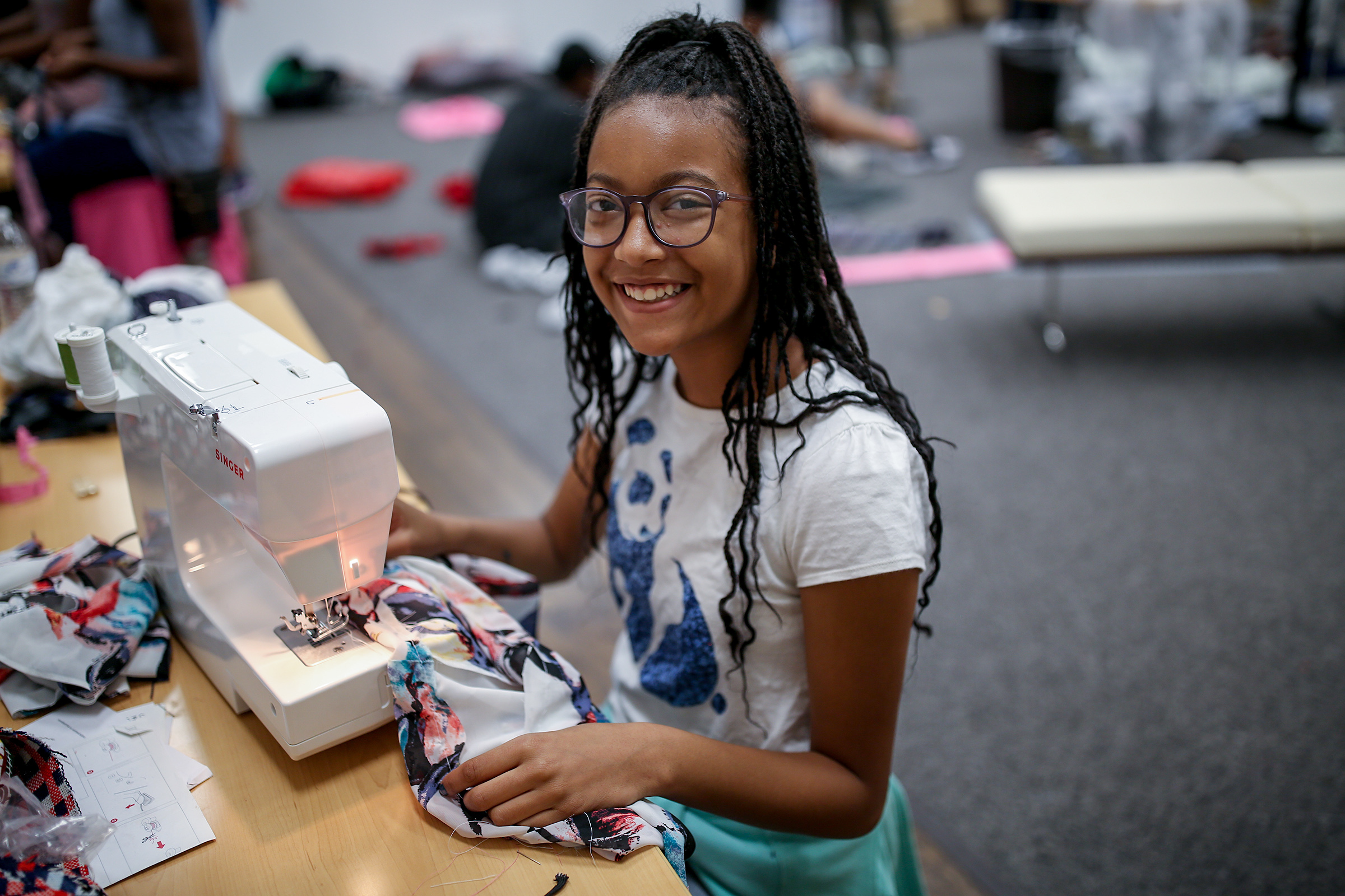 """A camper is all smiles as she learns how to use a sewing machine at the """"Say it isn't so, I will learn how to sew"""" summer camp at JSU led by Shonda McCarthy, director of JSU art galleries, and Kristen Martin, an entrepreneur and 2018 graduate of the College of Business. (Photo by Charles A. Smith/JSU)"""