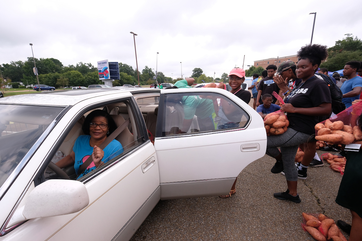 A gleeful patron is eager to receive bags of free sweet potatoes. (Photo by Charles A. Smith/JSU)