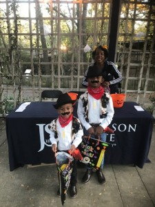 Carroll Frazier, administrative assistant/community outreach specialist for CUBD, provides treats to a couple of cowboys during Boo at the Zoo.