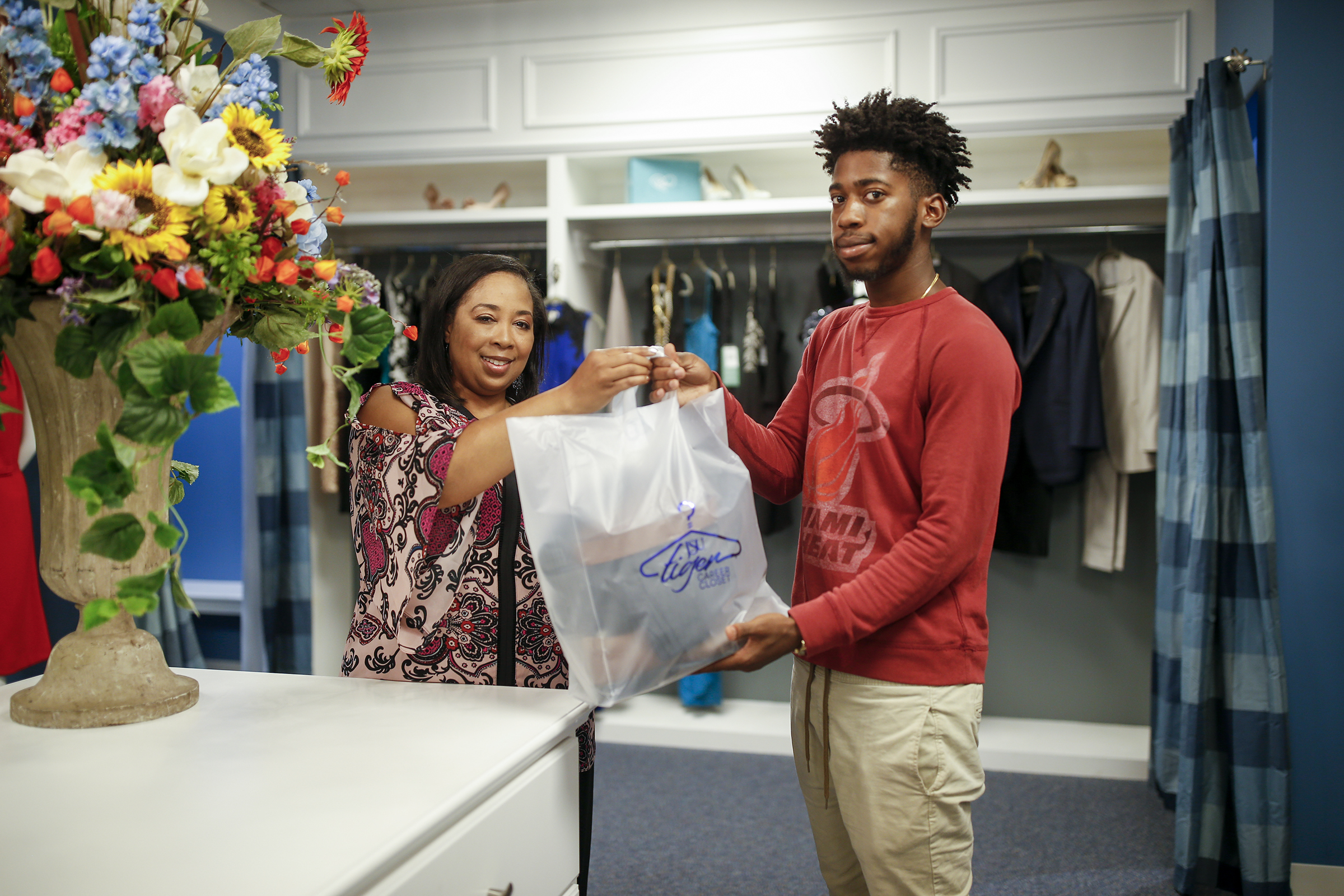 LaShanda Jordan JSU Executive Director Career Services Center gives Patrick Eldria, a sophomore business major his shopping bag filled with professional attire.