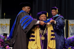 Dr. George French, president of Miles College in Birmingham, AL is hooded during the fall 2018 commencement exercise. (Charles A. Smith/University Communications)