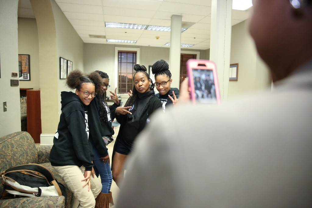 A group of students, along with Alexander, frolic in front of the camera. (Photo by Kentrice S. Rush/JSU)
