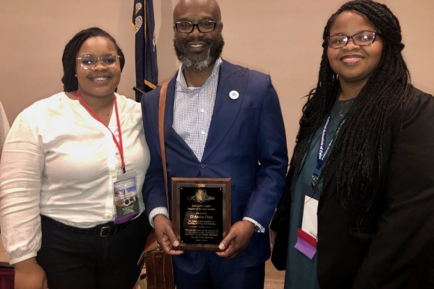 Dr. D'Andra Orey, professor of political science, poses with students after accepting his Anna Julia Cooper Teacher of the Year Award in Baton Rouge, LA.