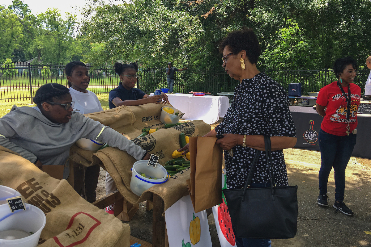 Blackburn Laboratory Middle School students assist a customer with the purchase of vegetables from their student-led Farmers Market. The event was held Wednesday, May 22, in partnership with Jackson State University and supported by  sponsors and the community. (Photo by Charles A. Smith/JSU)