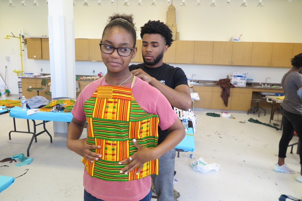 Zacchaeus Simmons, owner of the clothing brand Zacari, helps Kennedy Anderson, a seventh grader, with a top she designed. Simmons, a JSU alum, said that helping students learn about managing a business is his way of giving back. (Photo by Rachel James-Terry/JSU)