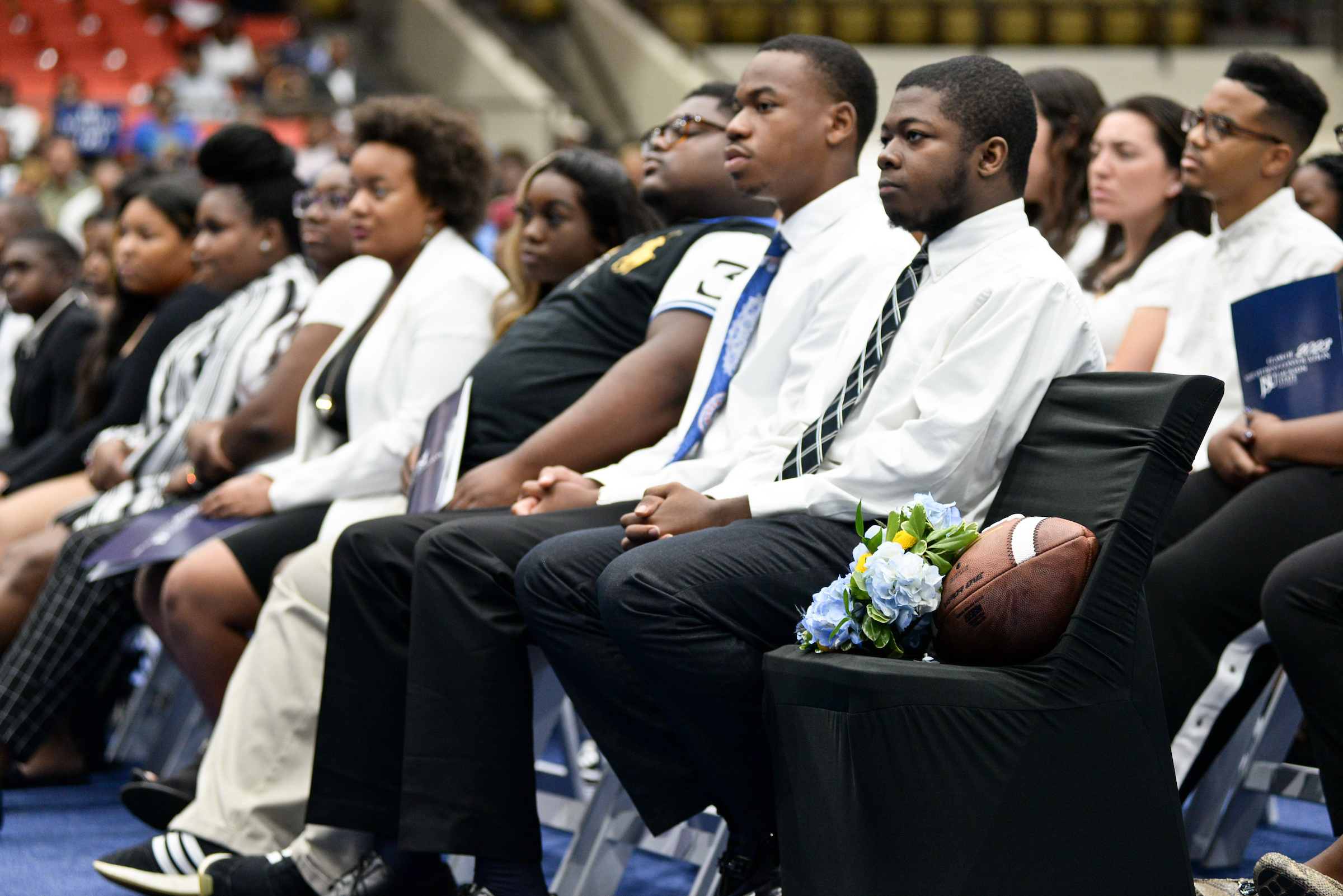 With a football placed on an empty chair, a moment of silence is observed during New Student Convocation as students pay respect to incoming JSU football player Leroy Hawkins, 17, who died tragically in early June in Dallas. He was a Top 300 offensive lineman and, reportedly, was 34th in Texas. (Photo by Darek Ashley/Special to JSU)