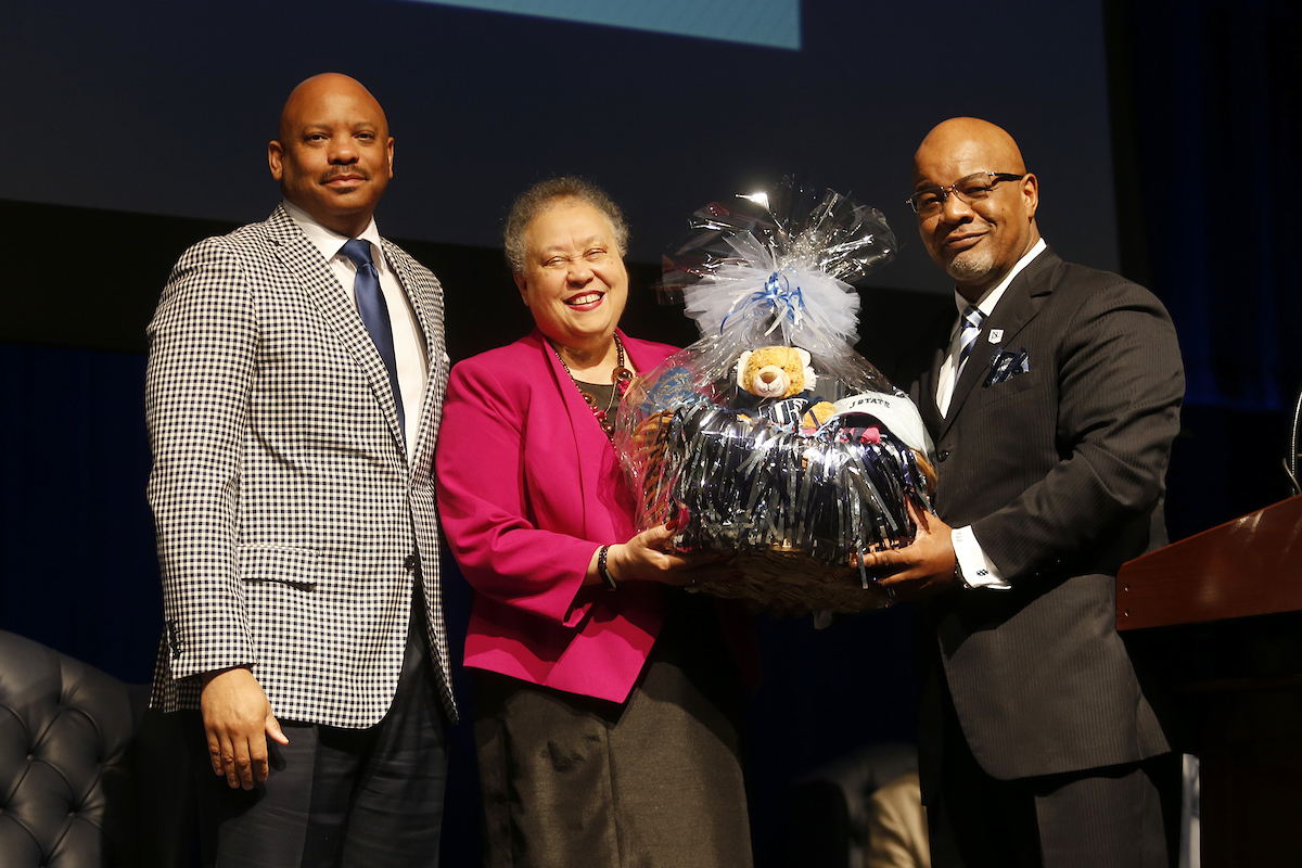 Bynum presents Wheelan with a basket that contains JSU memorabilia, souvenirs, keepsakes and other tokens. (Photo by Charles A. Smith/JSU)