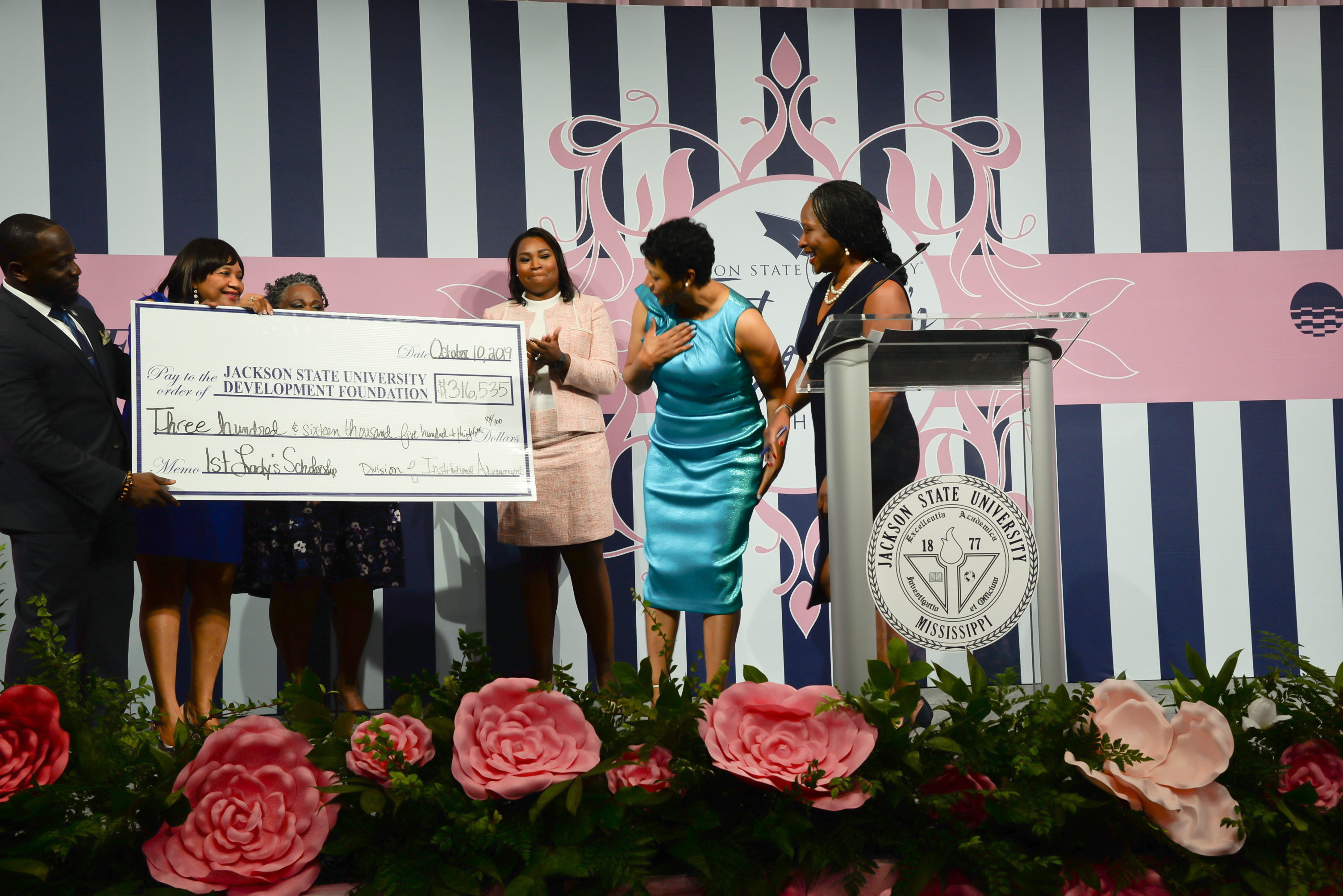 Astounded by the total amount raised for the second annual First Lady's Scholarship Luncheon, Deborah Bynum displays gratitude and joy during the on-stage check presentation.