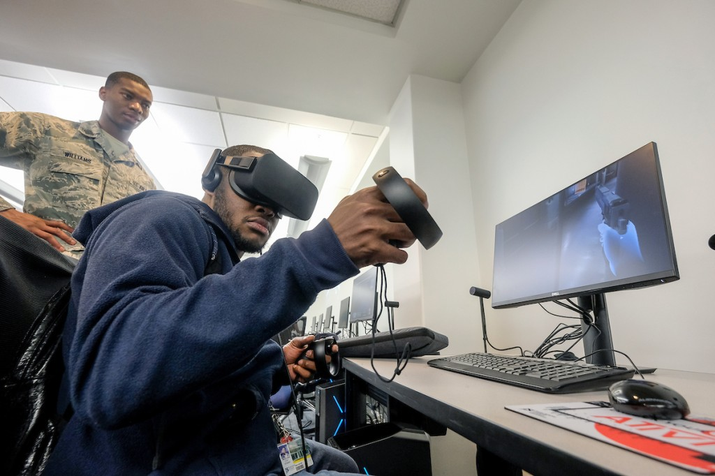 RIGHT: A fellow assists a student going through one of the VR simulations. (Photo by Charles A. Smith/JSU)