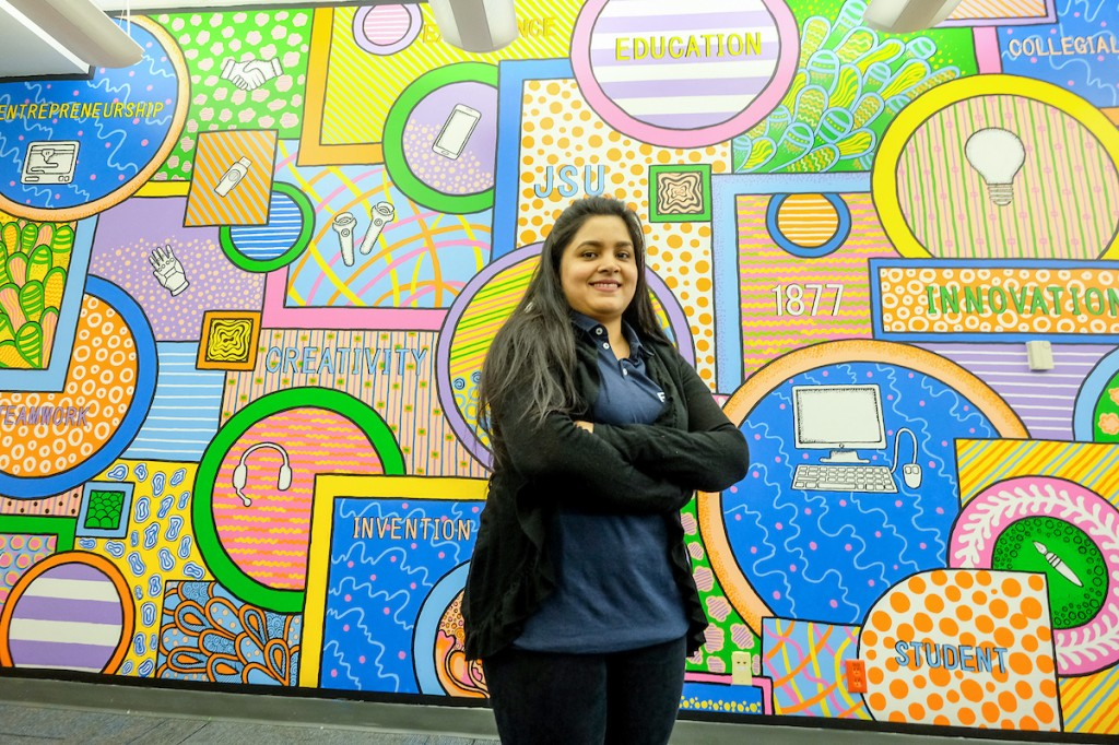 Dipannita Sasha, a senior graphic design major, stands in front of the brilliantly,  colorful mural she created for the center. (Photo by Charles A. Smith/JSU)