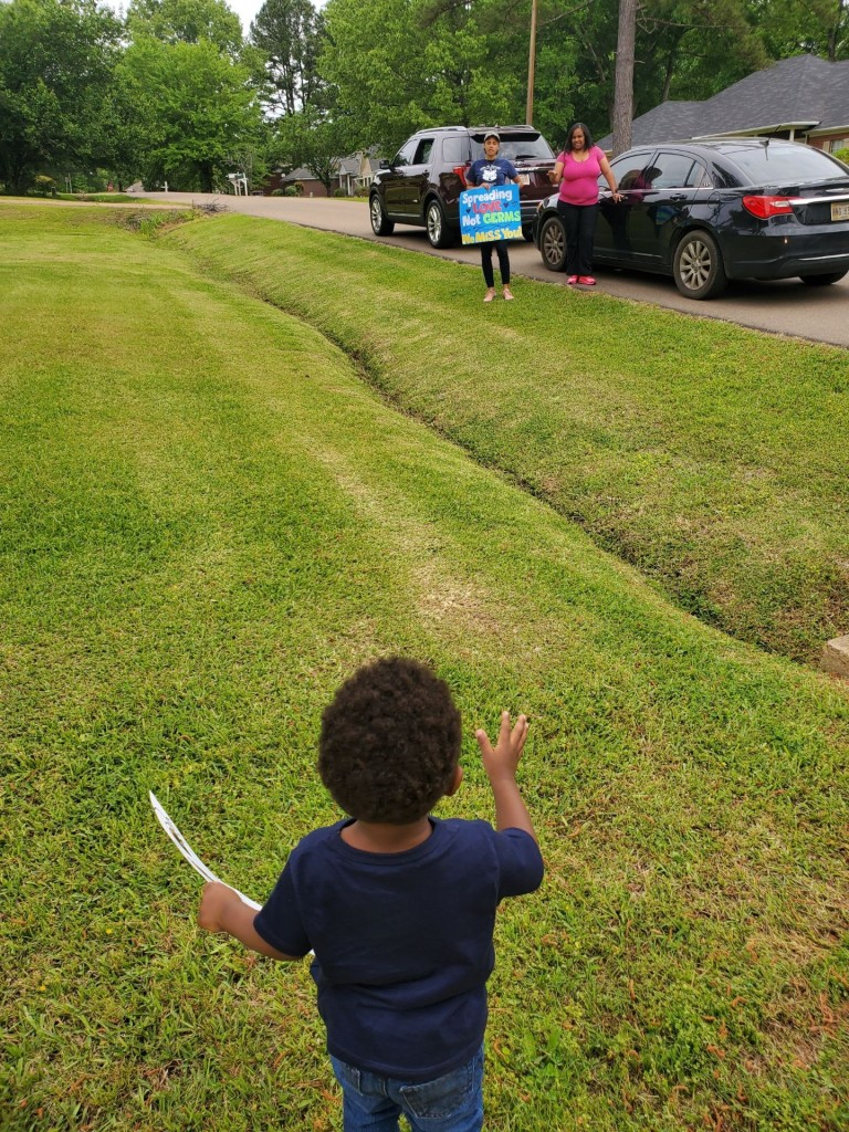 A student from the Lottie W. Thornton Early Childhood Center at JSU waves at his teachers, who hosted a car parade to show love and support to their preschoolers. (Photo special to JSU)