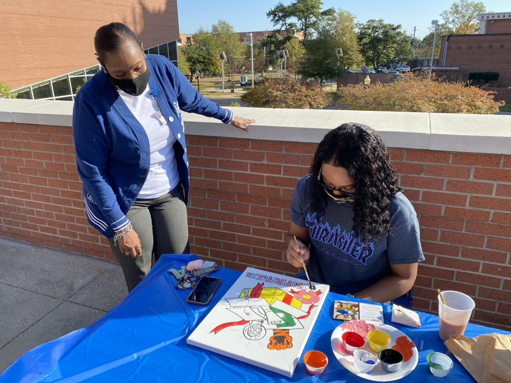 A first-generation student participates in a Patio Paint Kickback at the Student Center.