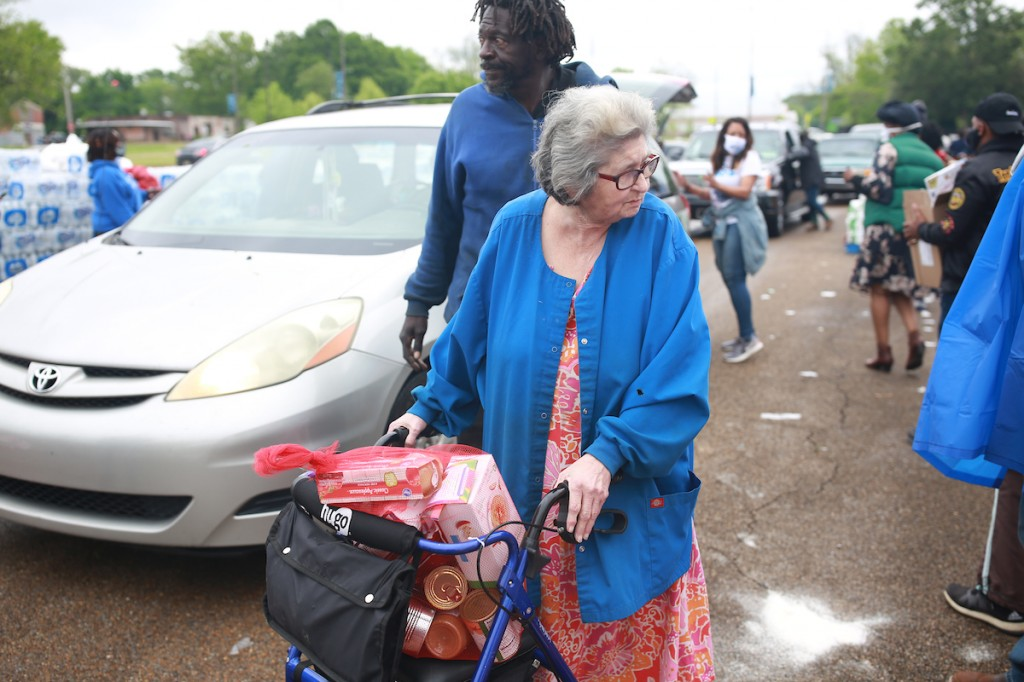 Marge Lairg walked to the event with help from John Slater. She said the food will help feed her great-grandson. (Photo by William H. Kelly III/JSU)